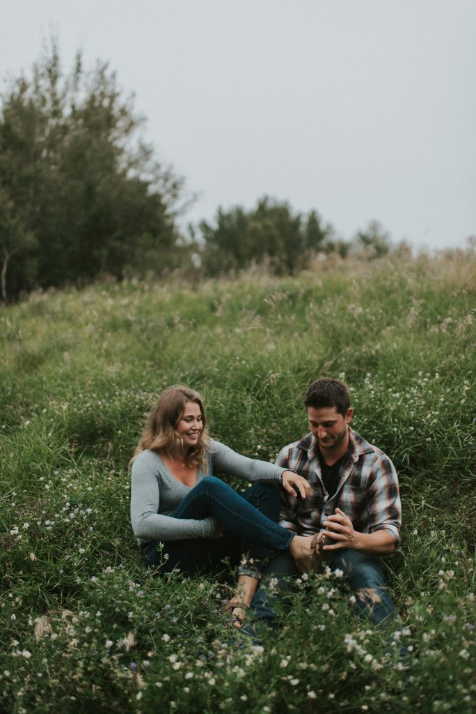 Engaged couple sits in field of green grass