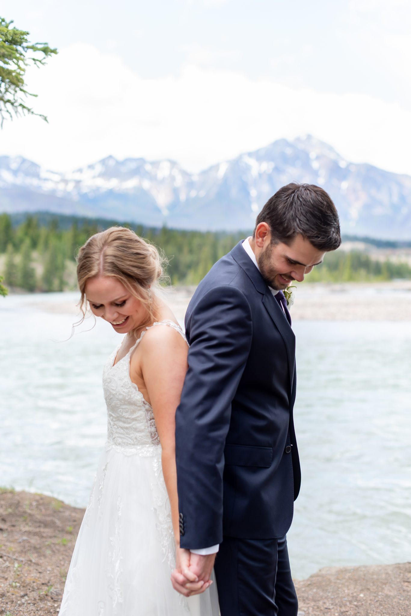 Bride and groom pose hand in hand in Jasper National Park with Pyramid Mountain in the background