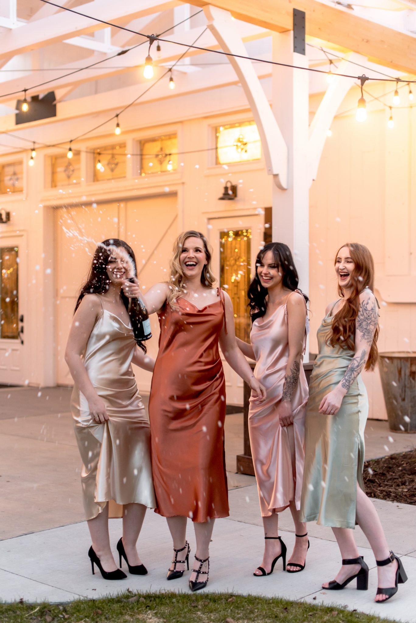 Bridesmaids pop a bottle of champagne on the patio at the Whitewood Barn, one of Alberta's premier luxury wedding venues
