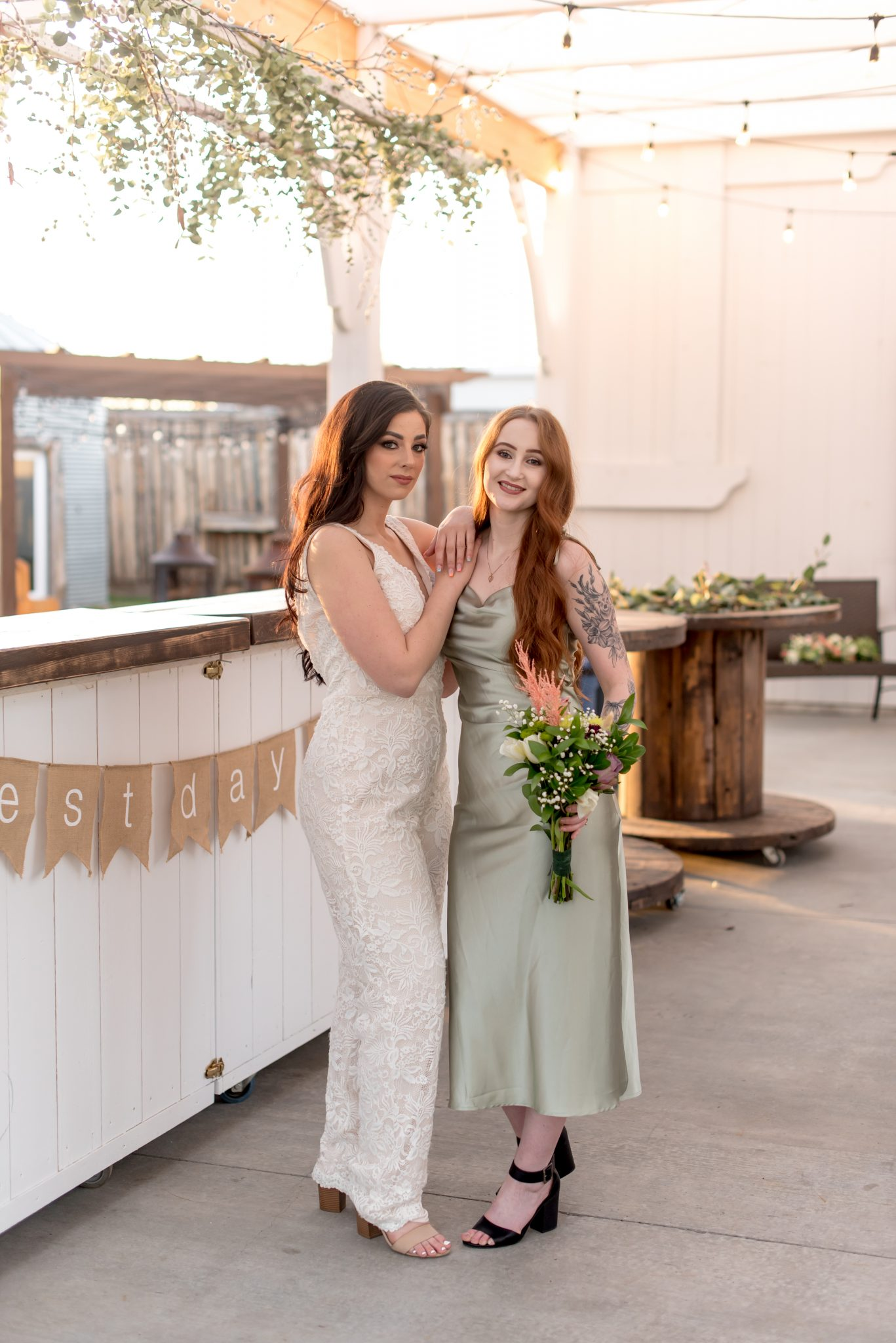 Bride in a white lace jumpsuit and bridesmaid in a green sage midi slip at Whitewood Barn, Alberta's luxury wedding veune