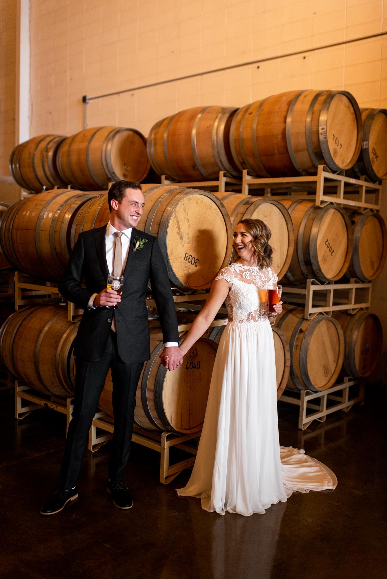 Alberta brewery wedding bride and groom in front of beer barrels