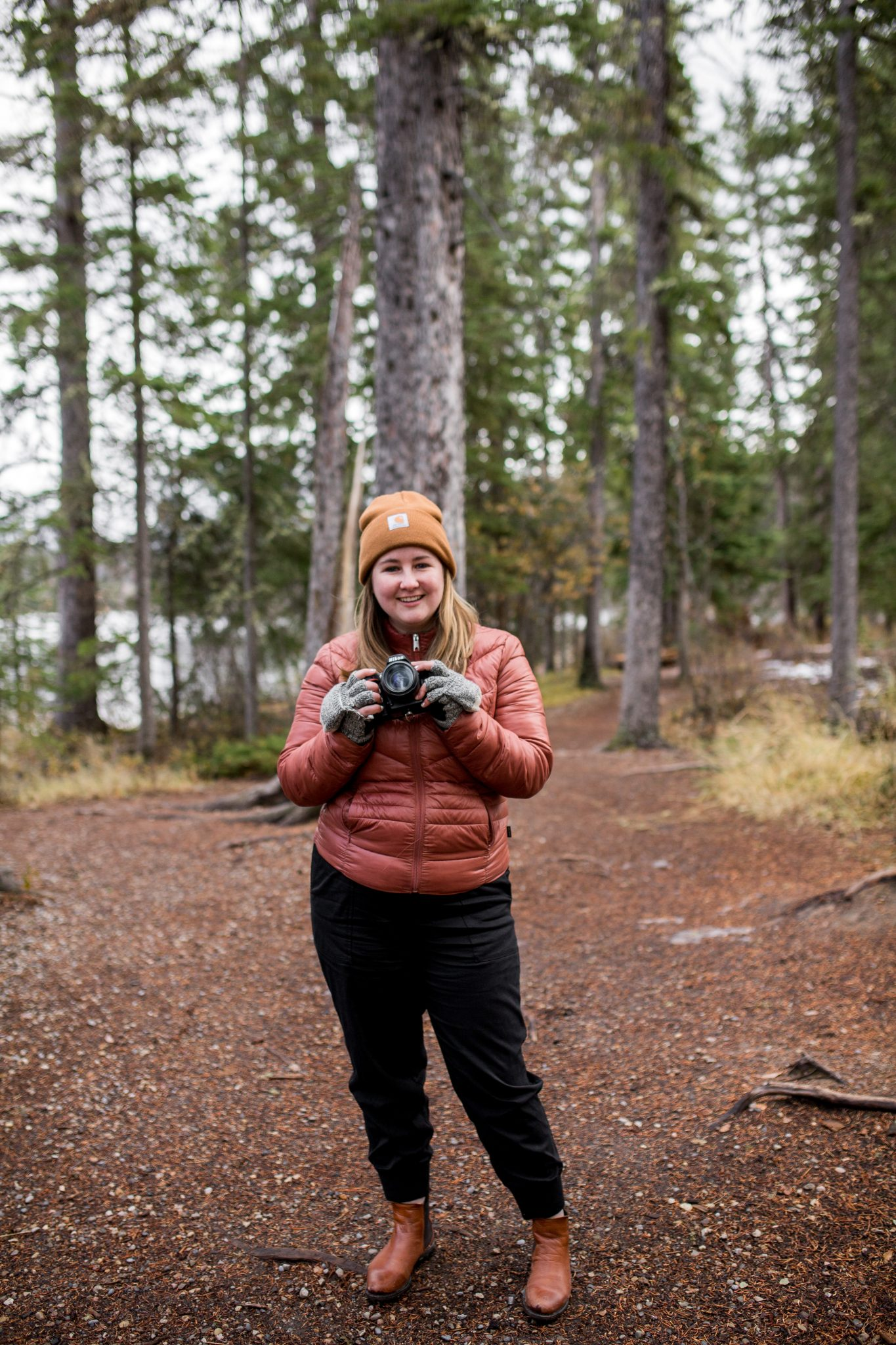Janelle Dudzic of Janelle Dudzic Photography poses with her camera in an area of Pine trees at Pyramid Lake in Jasper National Park