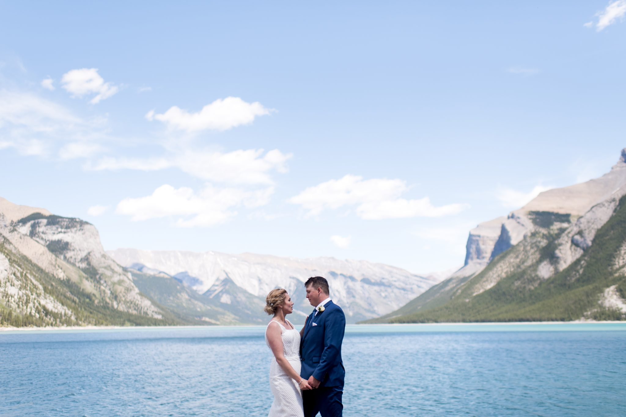Bride and groom stand on the shore of Lake Minnewanka on their wedding day