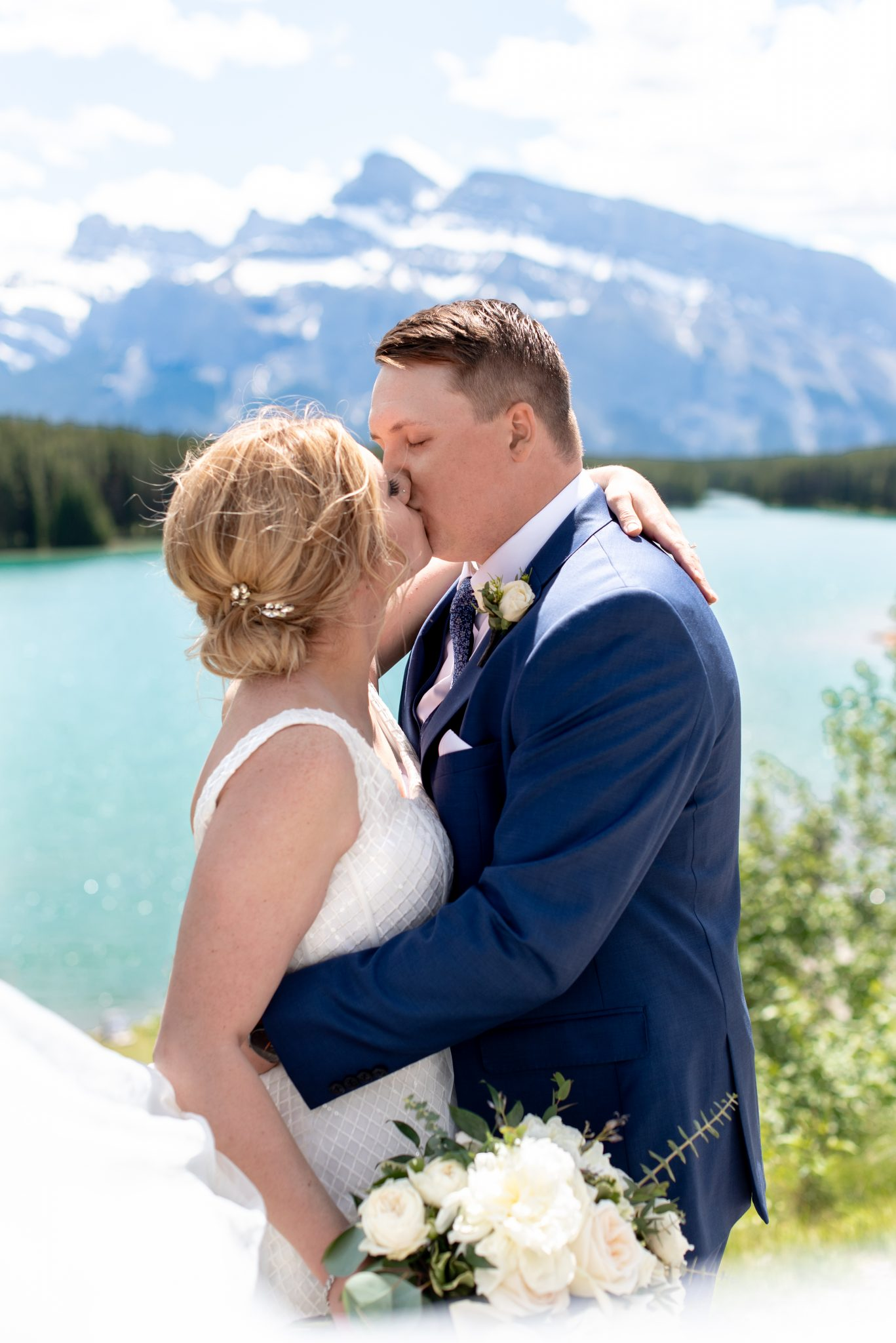 Bride and groom share a kiss above the shores of Two Jack Lake in Banff National Park