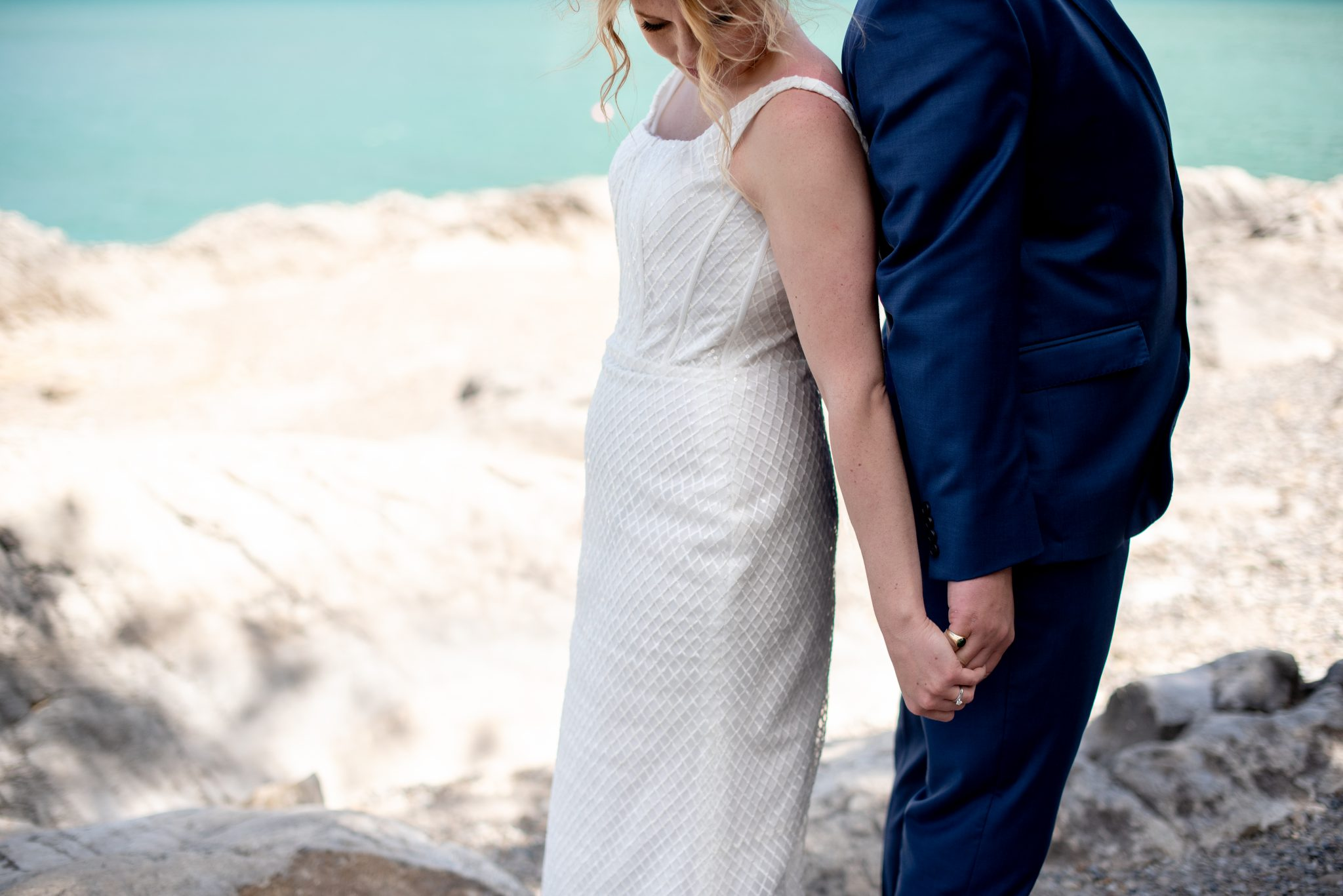 Bride and groom hold hands on the shore of Lake Minnewanka