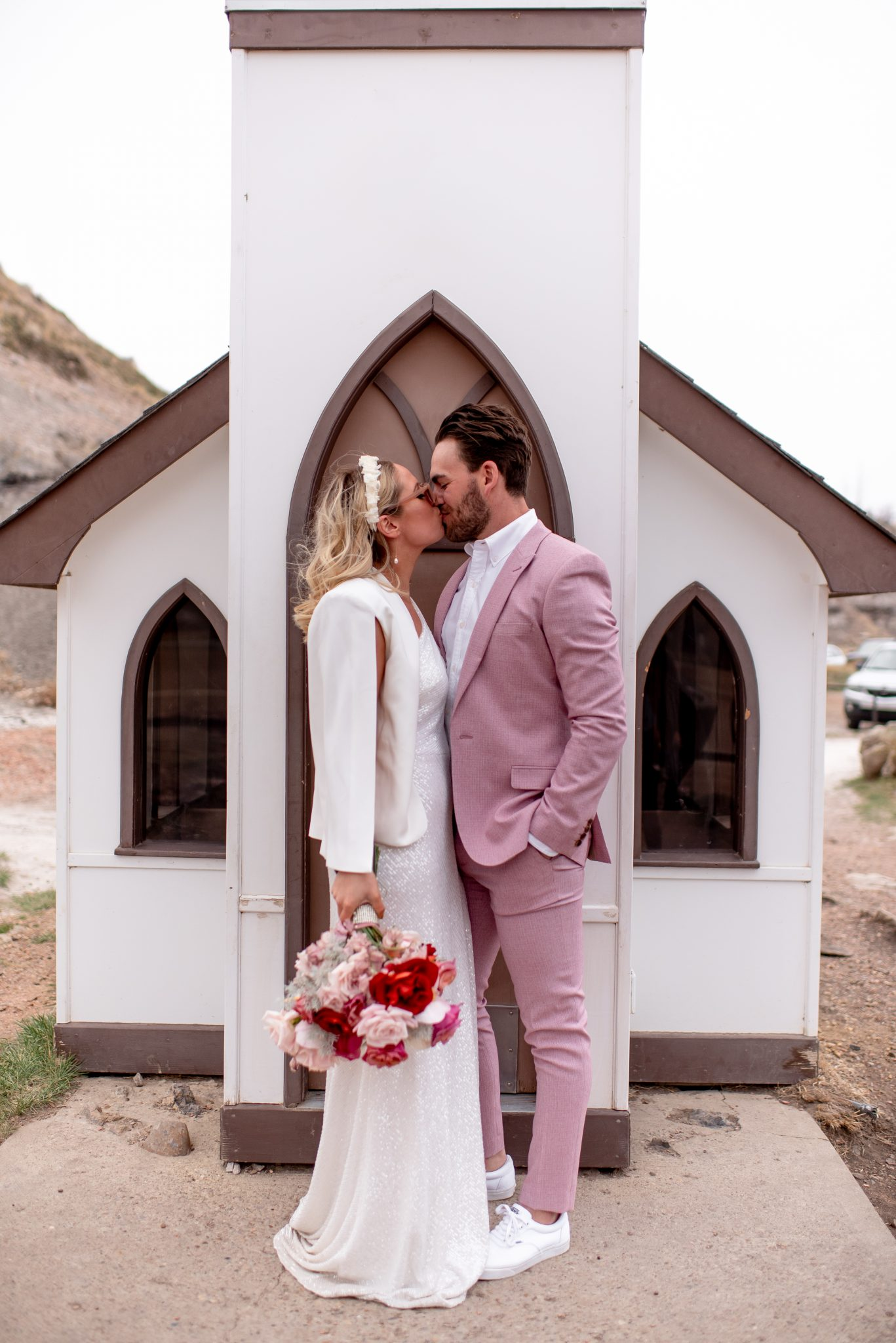 Boho wedding attire inspiration with a groom in a pink suit and bride wearing a crepe cape for a Drumheller Elopement