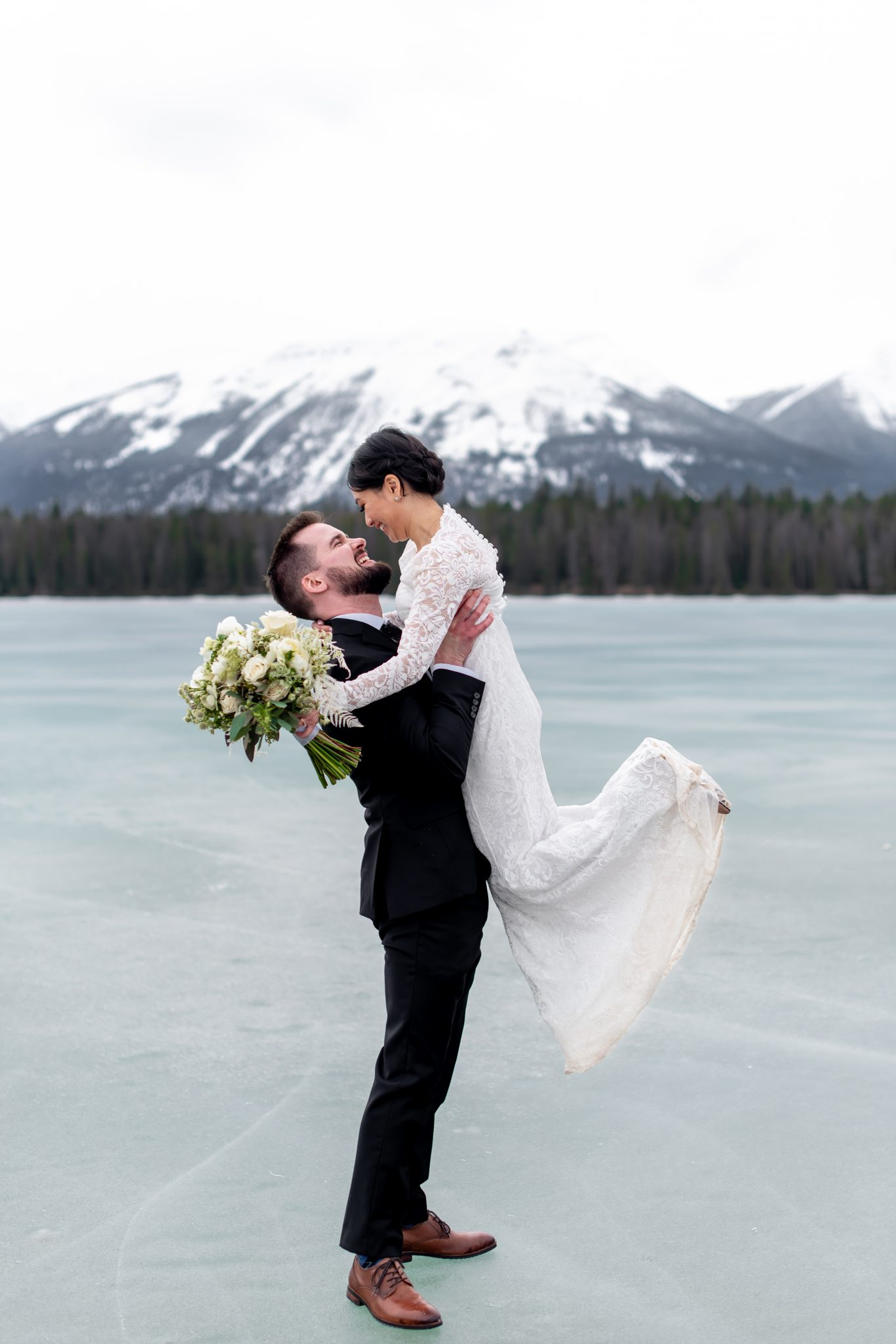 Bride and groom pose on the ice at Lake Annette for their Jasper National Park Elopement
