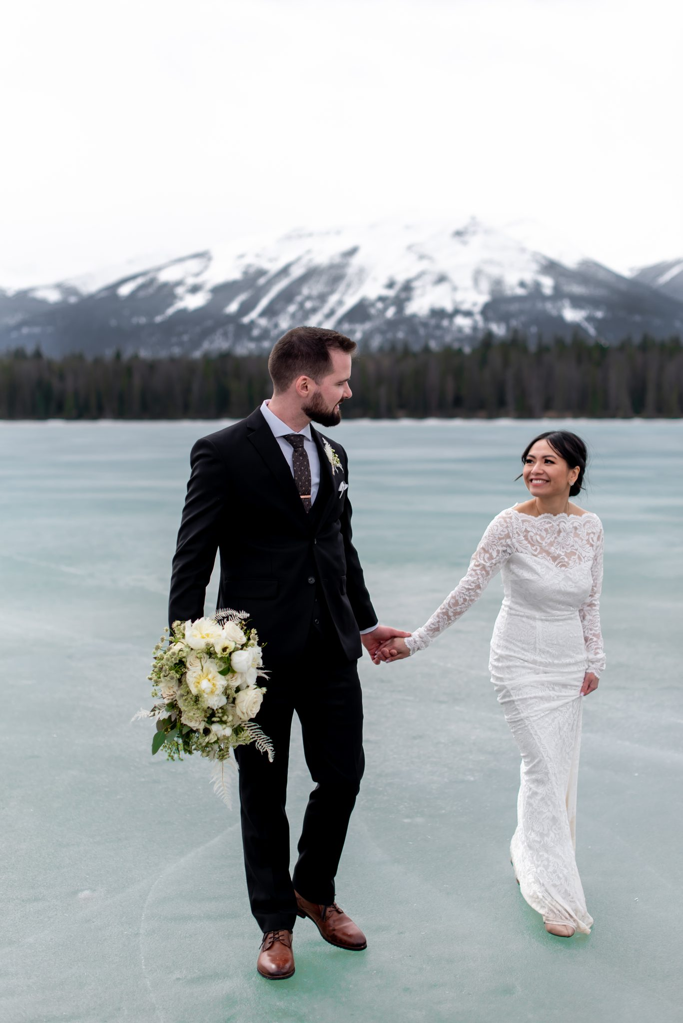 Bride and groom walk hand in hand across the icy Lake Annette for their Jasper National Park Elopement