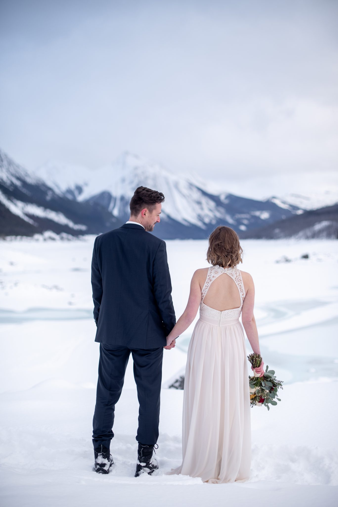Bride and groom look out over the mountain view at Medicine Lake for a winter elopement