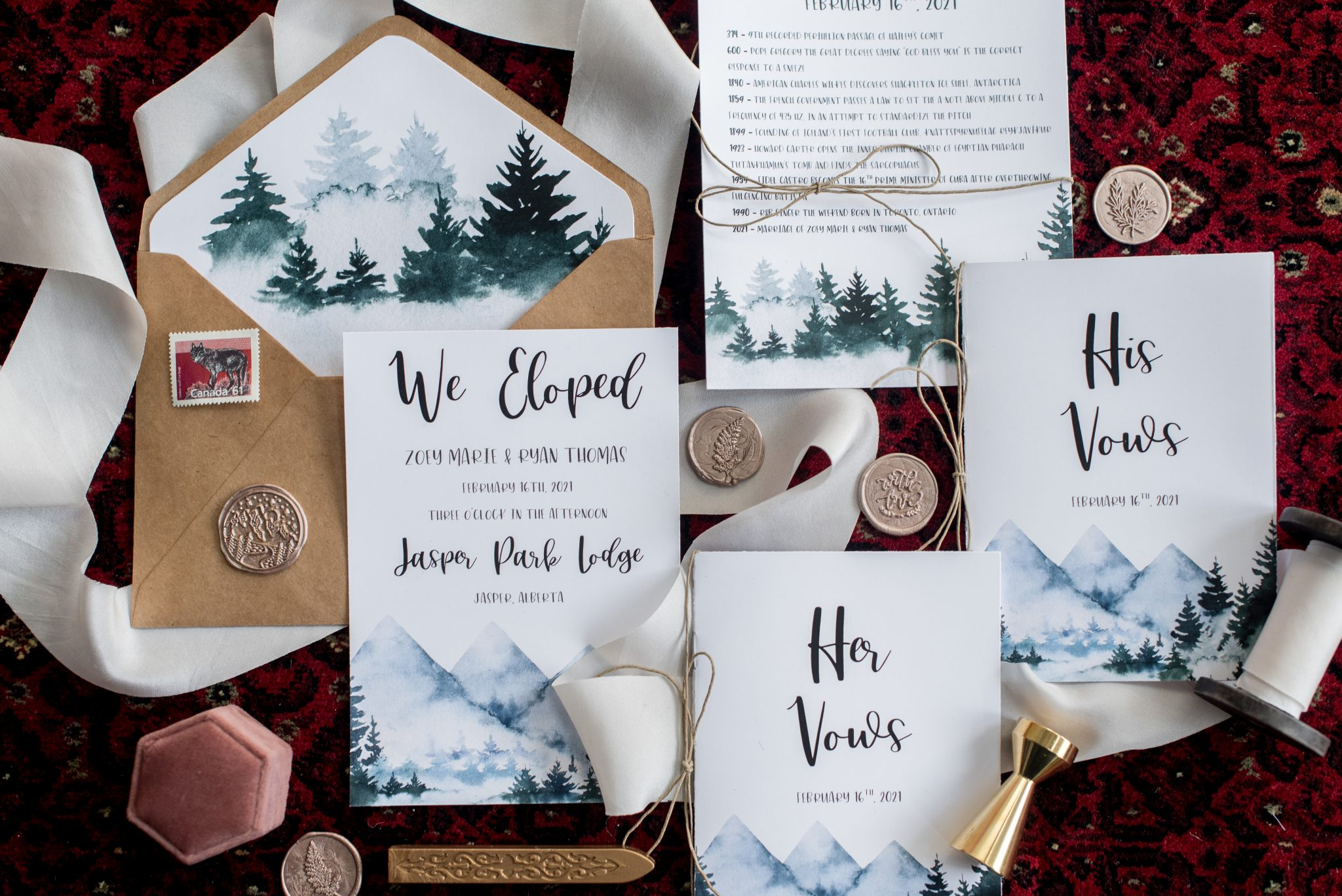 Elopement stationery set created by Loft Design Weddings displayed against a maroon rug