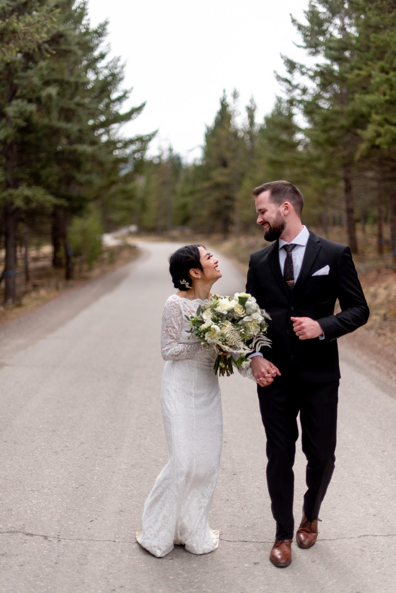 Bride and groom run on a road mountain road for their elopement in Jasper National Park