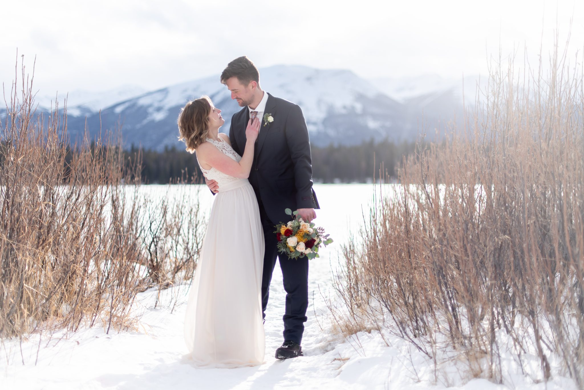 Bride and groom stand near Lake Annette for their winter elopement