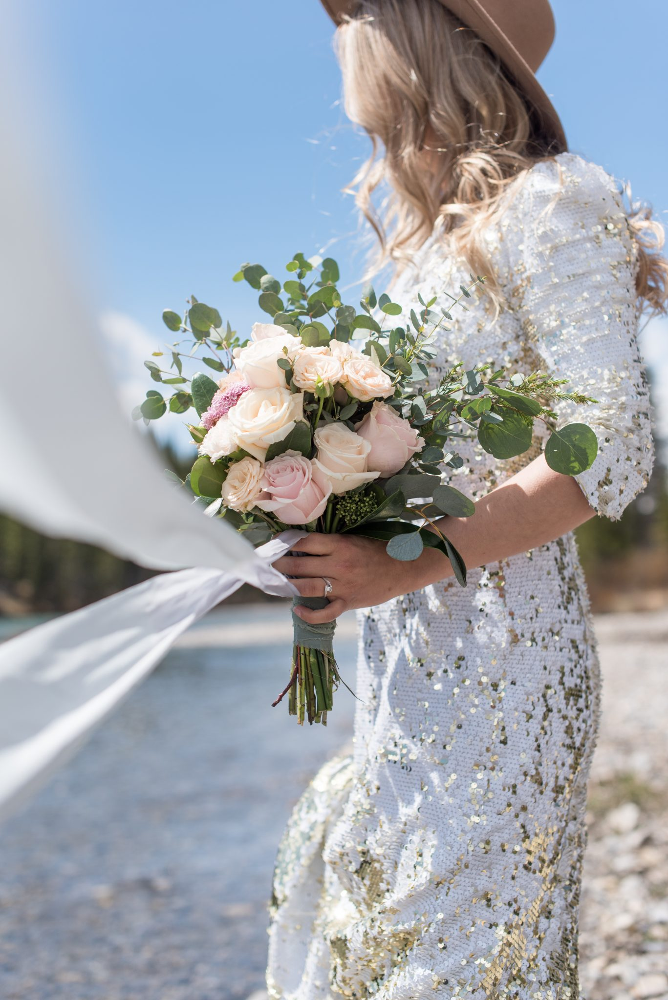 Gold sequin wedding dress against the blue sky of the Canadian Rocky Mountains