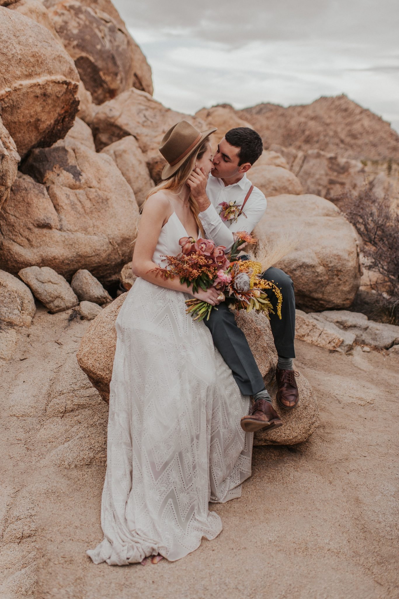Boho bride and groom share a kiss in Joshua Tree National Park