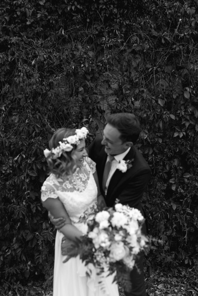 Bride and groom share a moment in front of a vine wall in the Edmonton river valley for their September wedding
