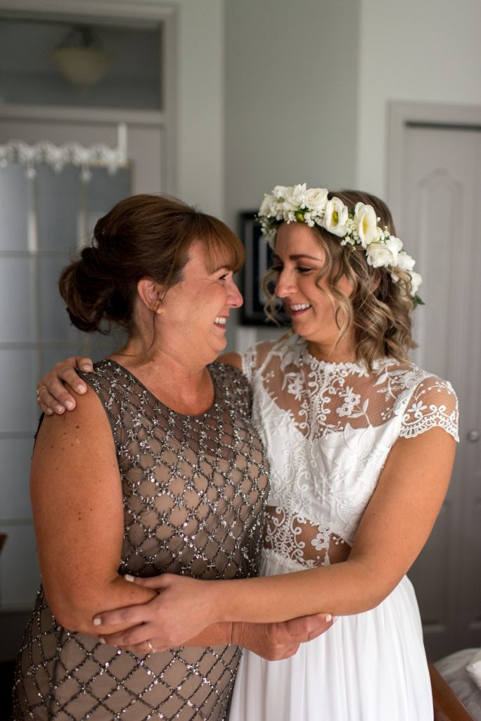 A bride in a white Abigail of Gardenia gown shares a moment with her mother