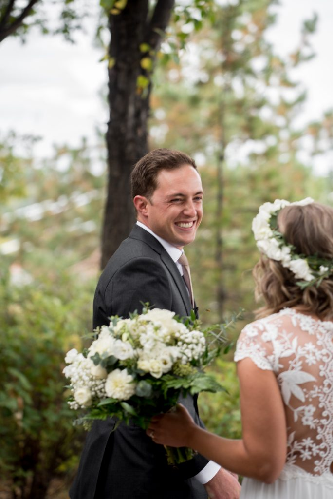 A groom shares a first look with his bride in Louise McKinney Park, Edmonton Alberta