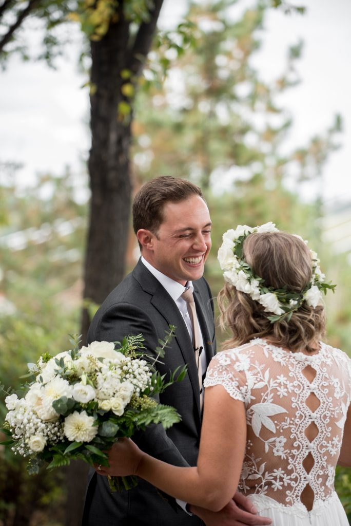 A groom shares a first look with his bride in Louise McKinney Park Edmonton Alberta