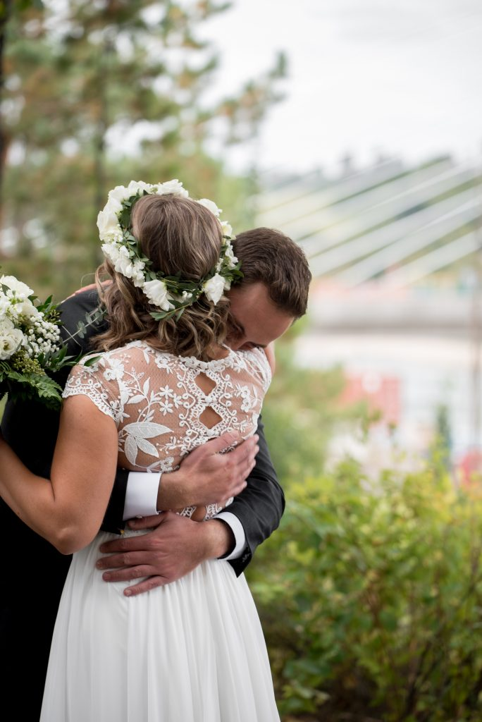 A groom hugs his bride moments after their first look in Louise McKinney Park Edmonton Alberta
