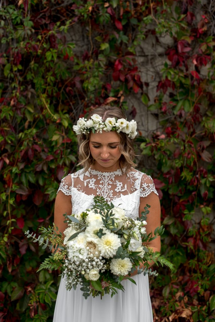 Bride in a white floral crown with matching bouquet poses in front of a vine wall in the Edmonton River Valley