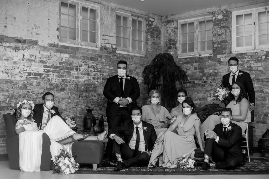 Large wedding party poses in Vouge style with their Covid-19 masks in the basement of Studio 96
