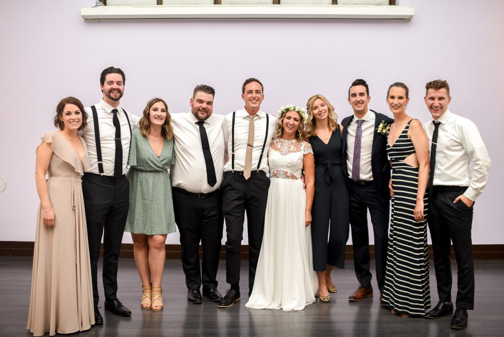Group portrait of friends posed together for a wedding at Studio 96