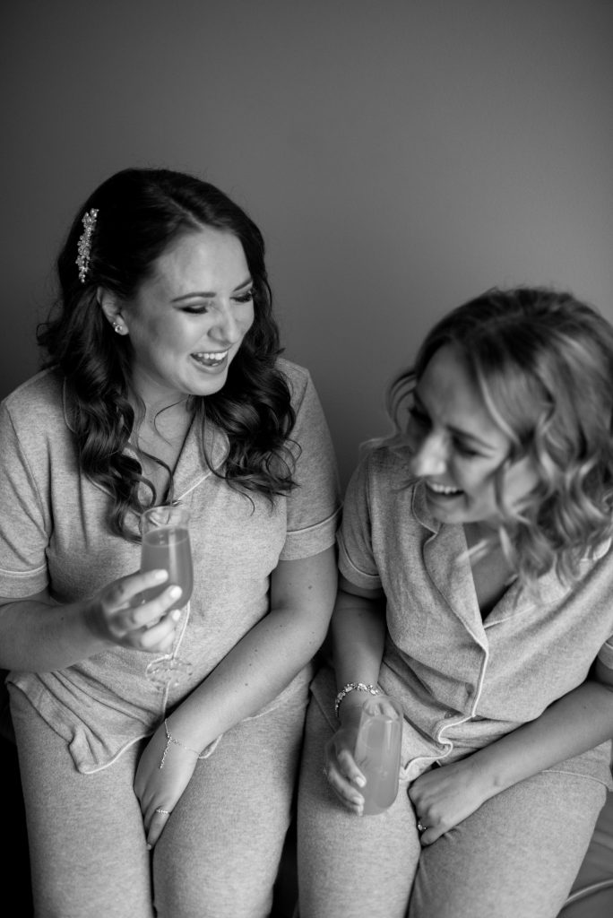 A black and white portrait of a bride and her maid of honour sharing a moment in their pjs