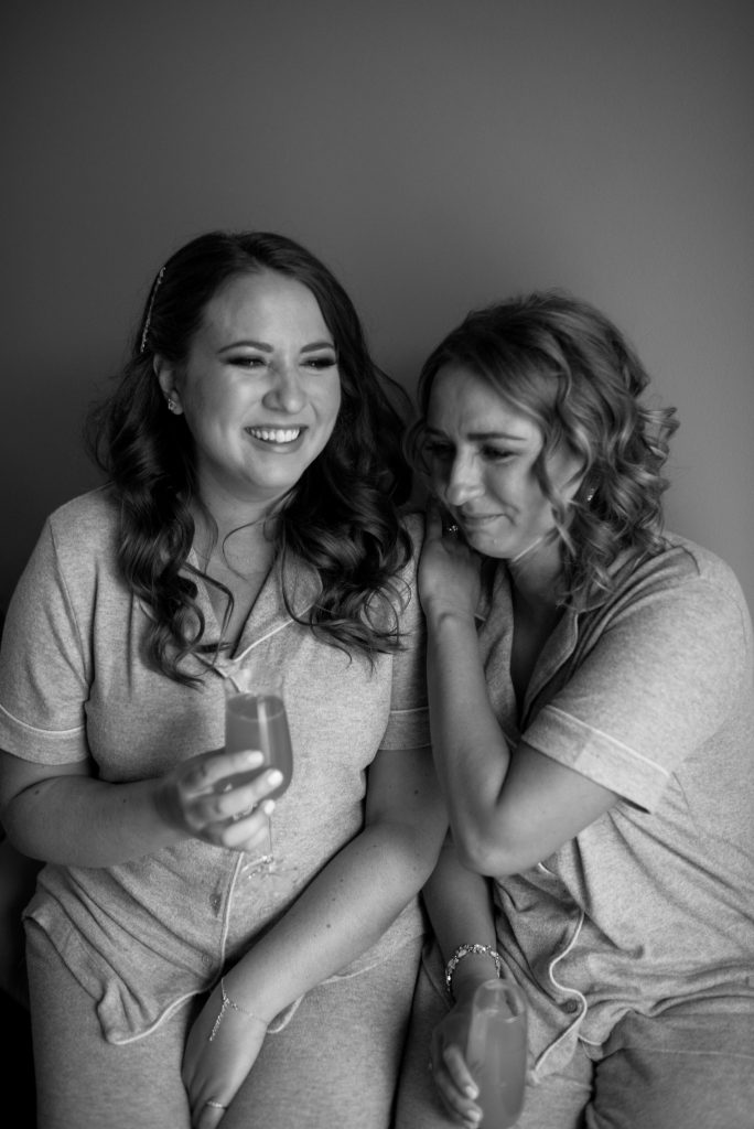 A black and white portrait of a bride and her maid of honor sharing a moment and mimosas