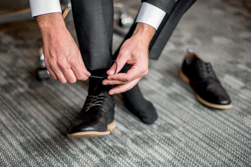 A groom ties his shoe laces on his wedding day