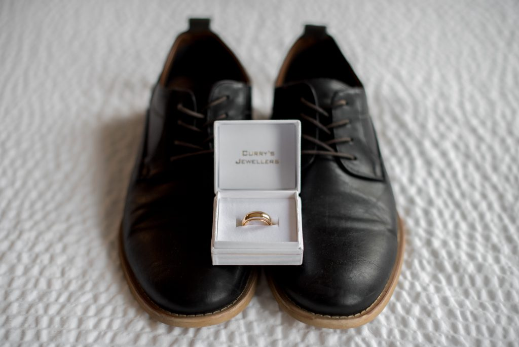 A gold men's wedding ring posed on top of a pair of black men's dress shoes