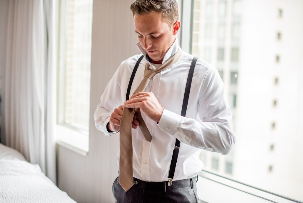 A groom ties his tie in a hotel room on his wedding day