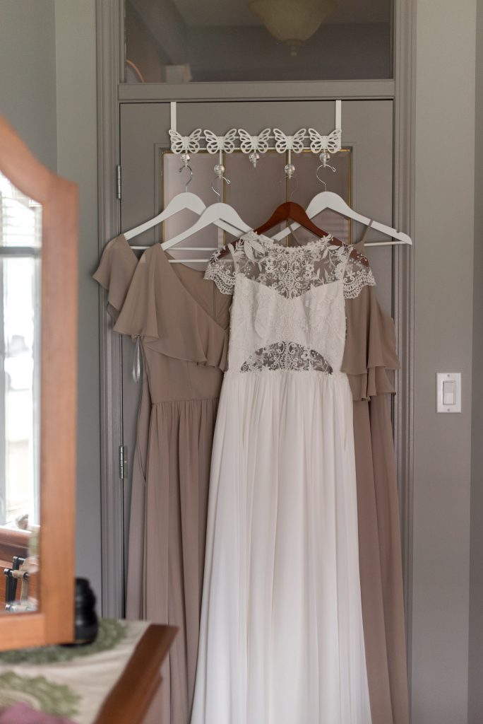 Abigail of Gardenia gown hanging with taupe bridesmaid dresses