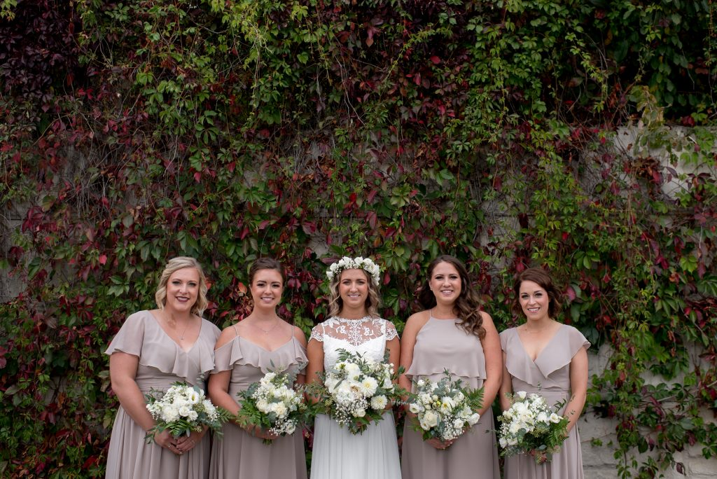 A bride and her bridesmaids pose in front of a vine wall in the Edmonton River Valley