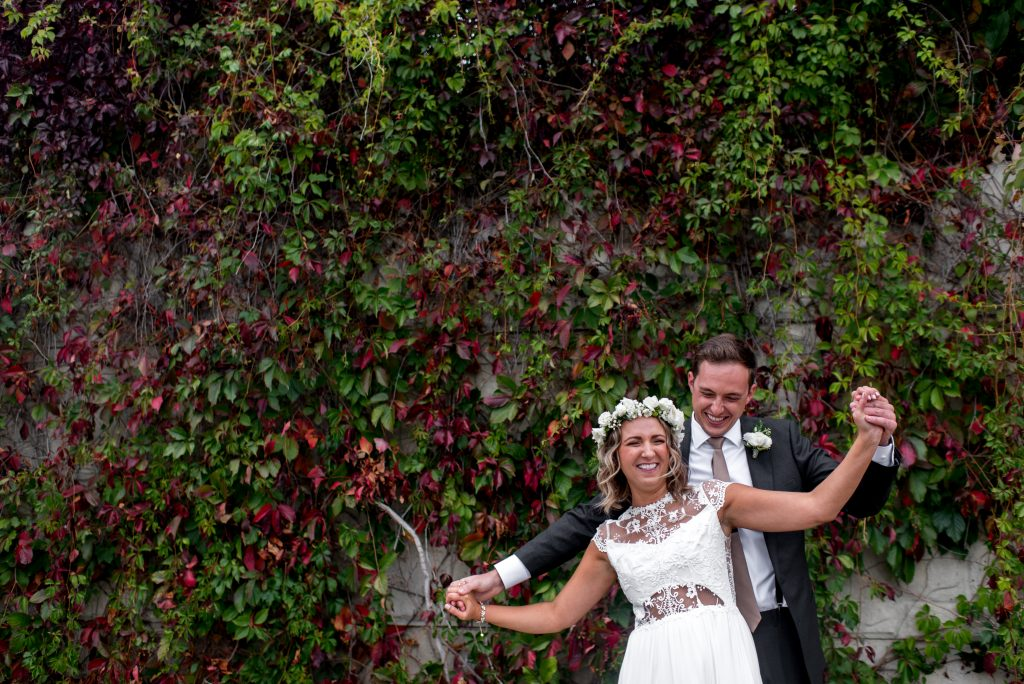 Bride and groom share a playful moment in front of a vine wall in the Edmonton river valley