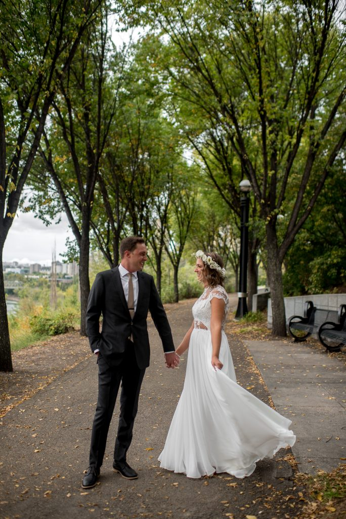 Bride and groom walk along a pathway for Edmonton river valley wedding photos in Louise McKinney Park