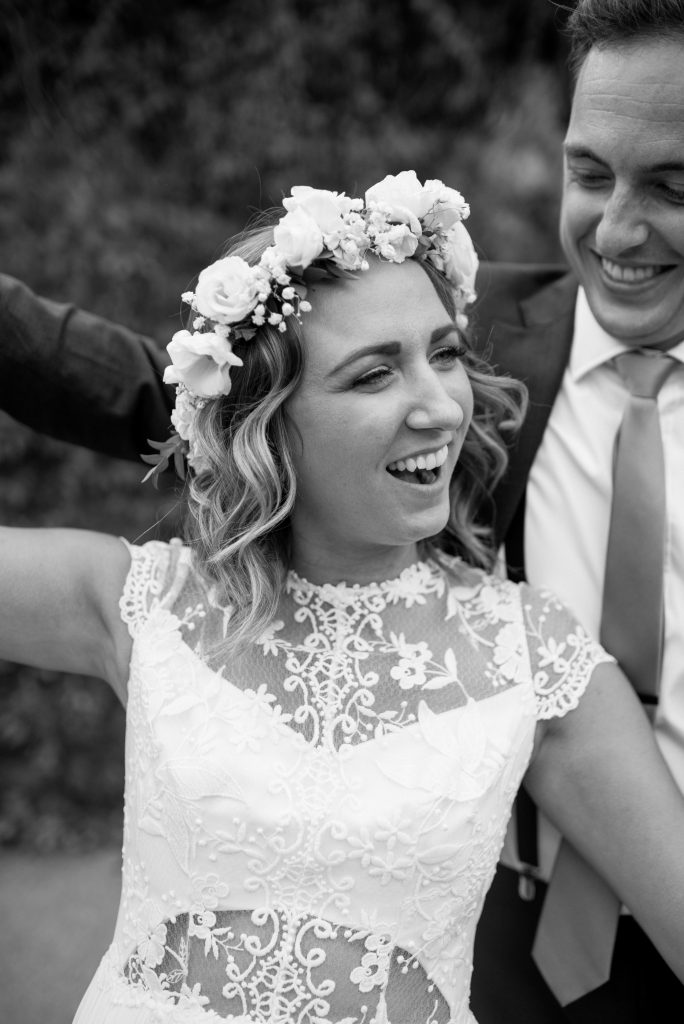 Bride wearing a brilliant white flower crown shares a playful moment with her groom