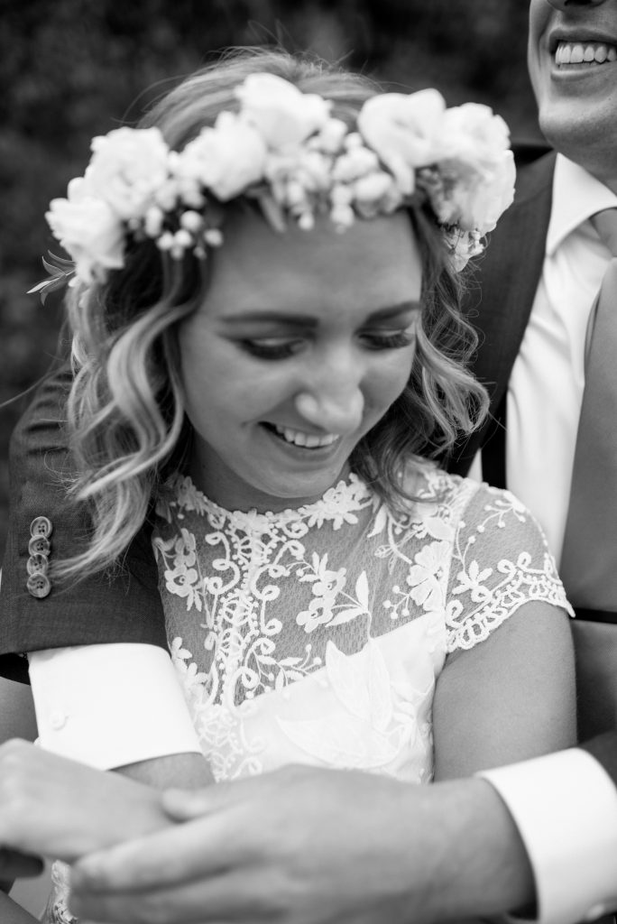 Bride in a brilliant white floral crown shares a playful moment with her groom