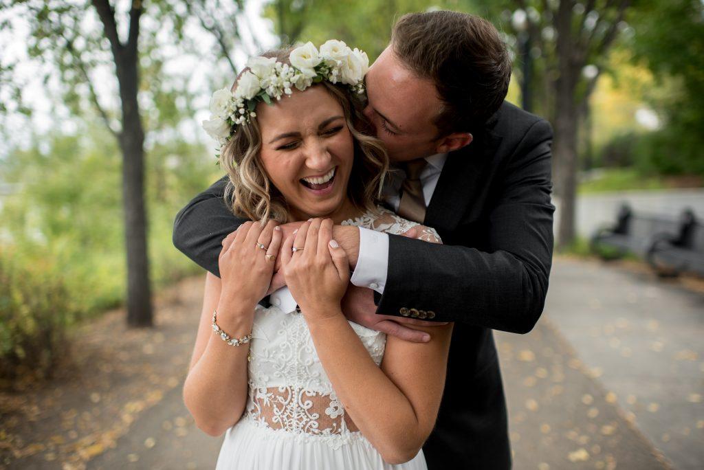 A groom kisses his bride on the cheek in Louise McKinney Park Edmonton Alberta on a Fall Edmonton River Valley Wedding