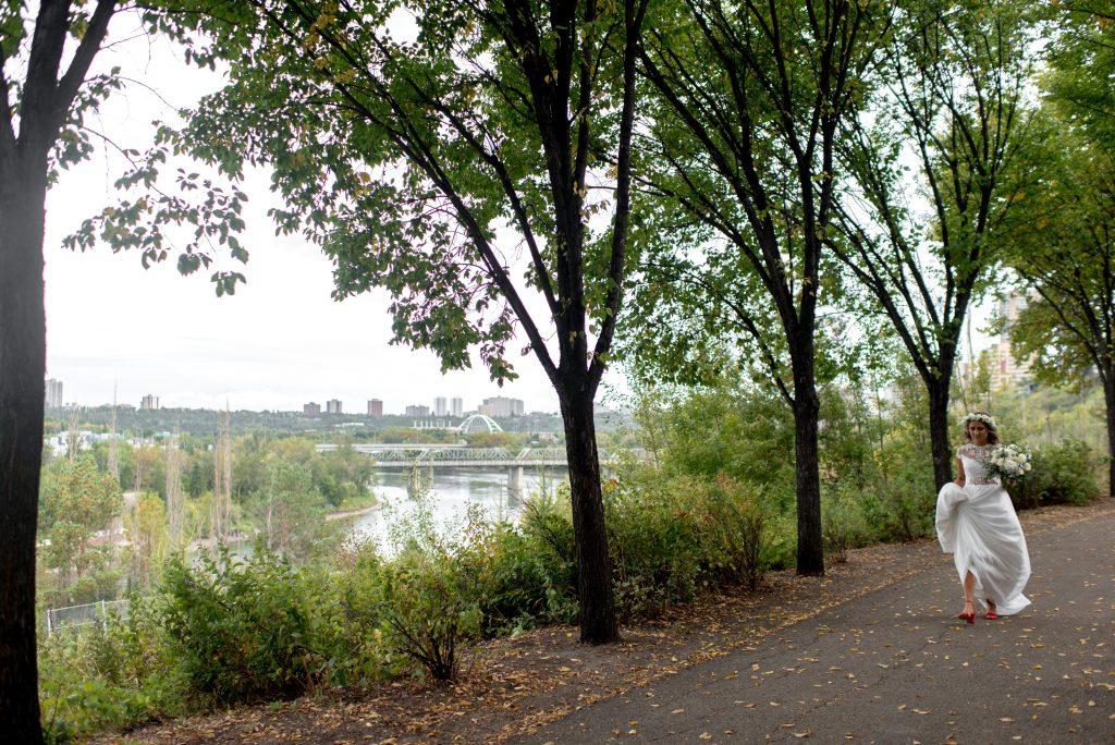 A bride in a Abigail of Gardenia walks through Louise Mckinney Park in the Edmonton River Valley