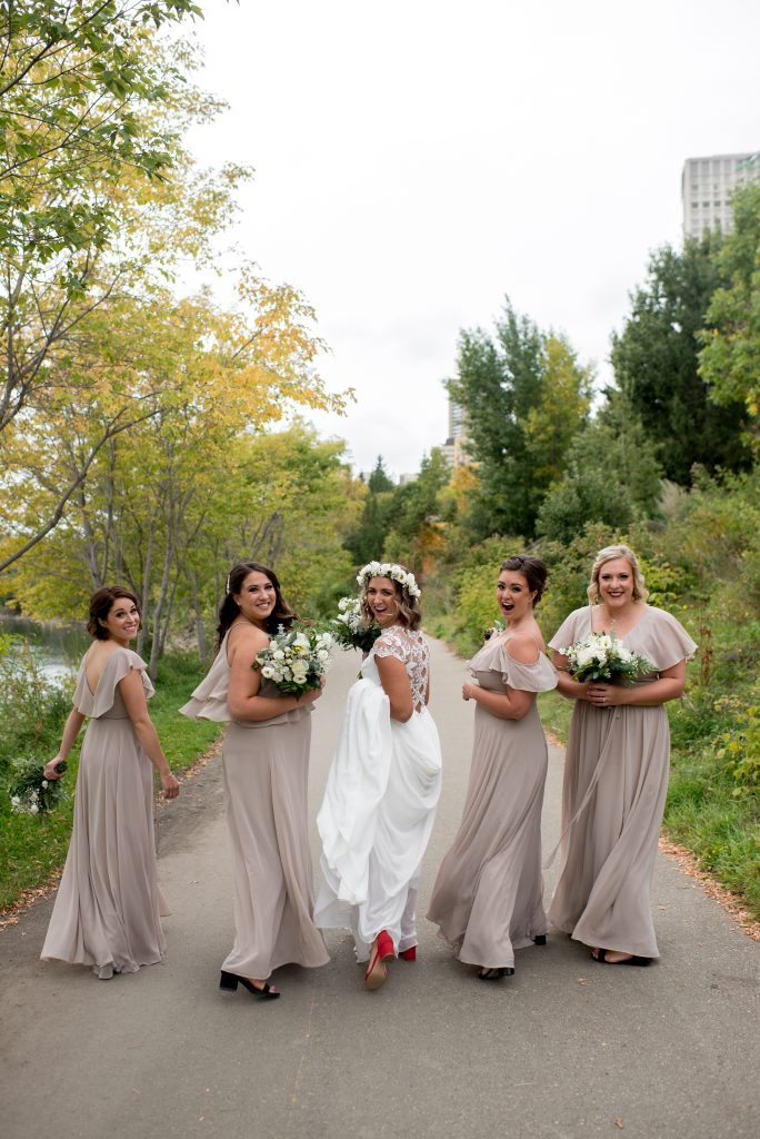 Bridesmaids in taupe gowns walk down the Edmonton river valley promenade for this September wedding