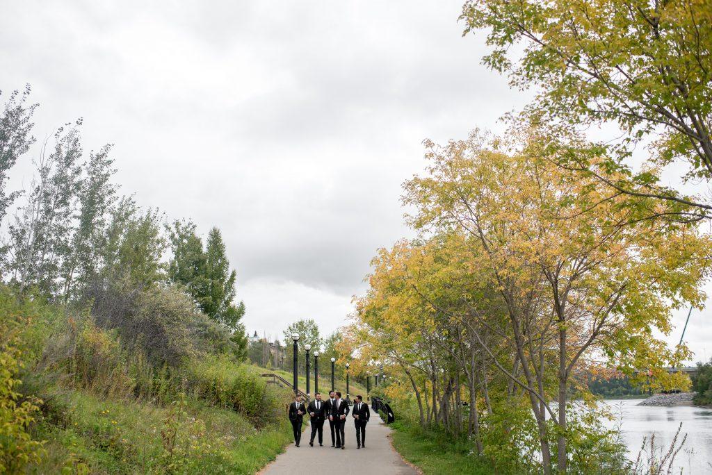 Groomsmen walk along a riverside promenade in the Edmonton River Valley for fall wedding photos