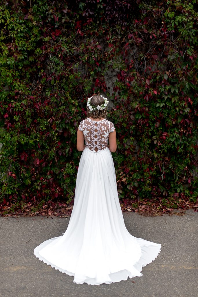 Bride in an Abigail of Gardenia wedding dress poses in front of a wall of vines in the Edmonton river valley