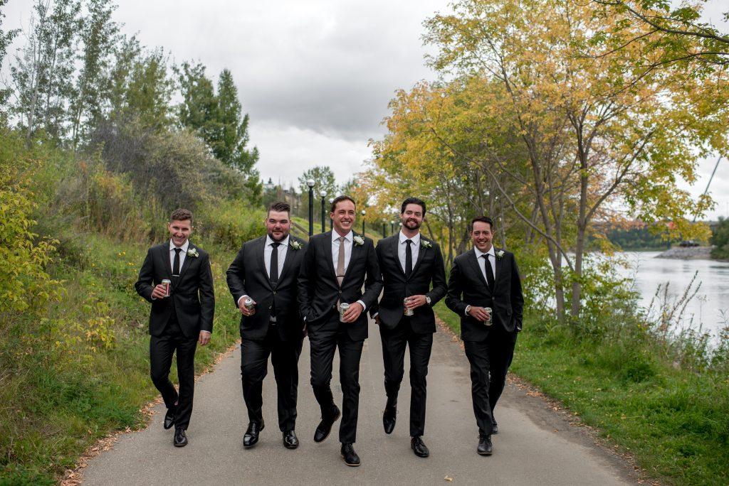 Groomsmen walk along the Edmonton river valley promenade for September wedding photos