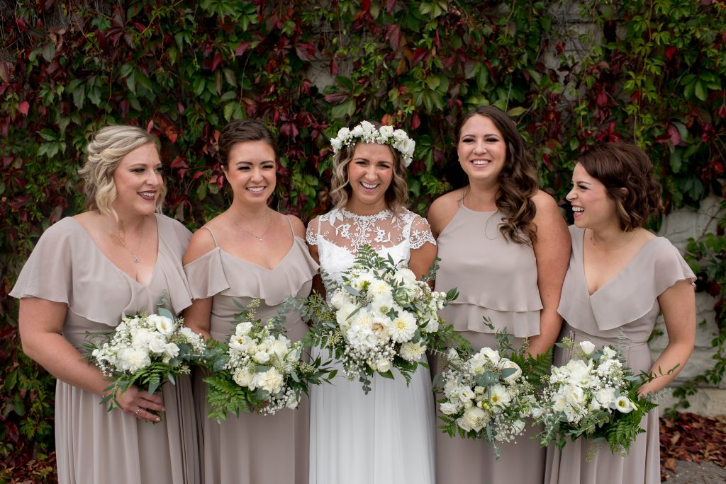 A bride and her bridesmaids in taupe bridesmaid gowns pose in front of a vine wall in the Edmonton River Valley for September wedding photos