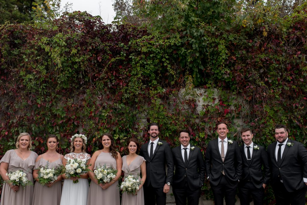 Edmonton bride and groom pose with their wedding party in the Edmonton River Valley in front of a vine wall