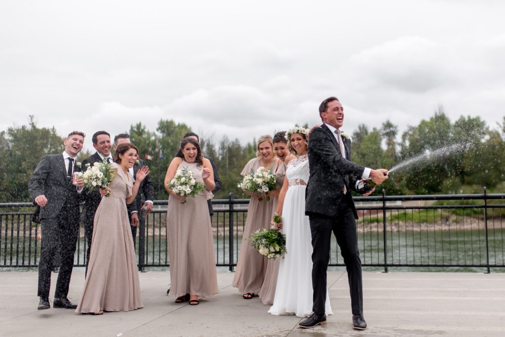 Groom opens and sprays a bottle of champagne