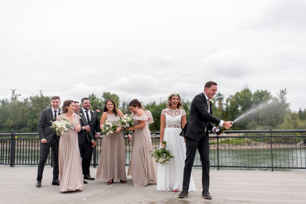 Groom opens a bottle of champagne