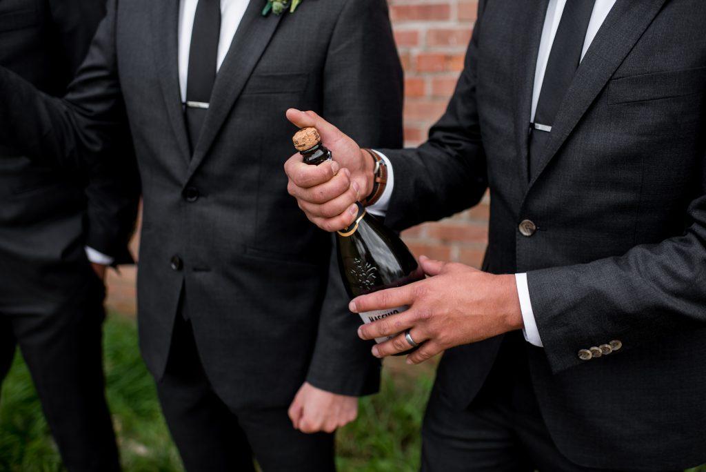 Groomsmen pops open a bottle of prosecco
