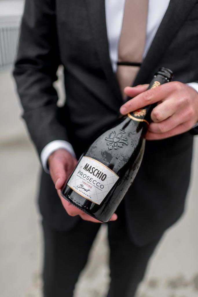 Groom holds a bottle of proseco