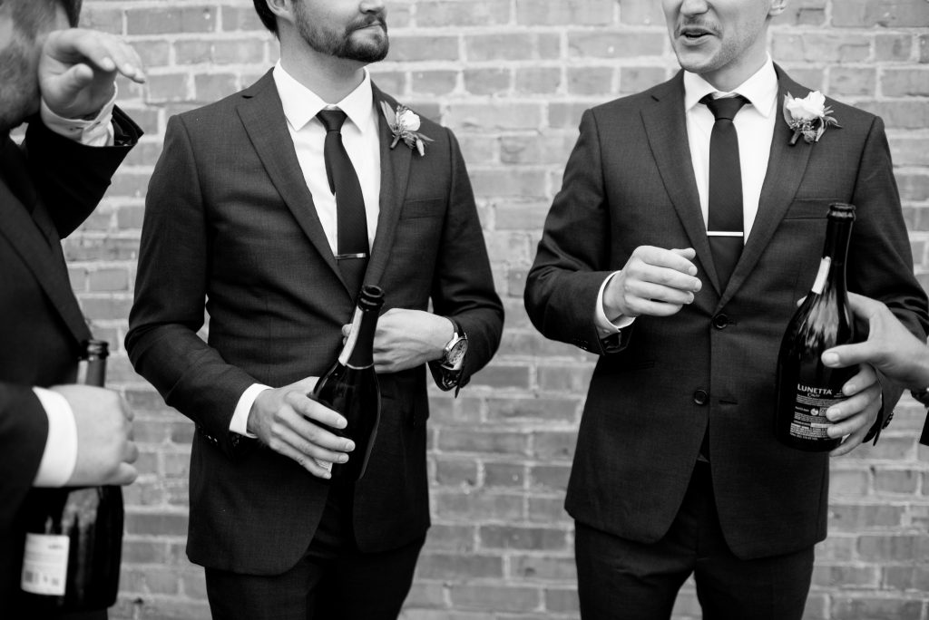 Groomsmen share bottles of Prosecco in downtown Edmonton Alberta on a fall wedding day